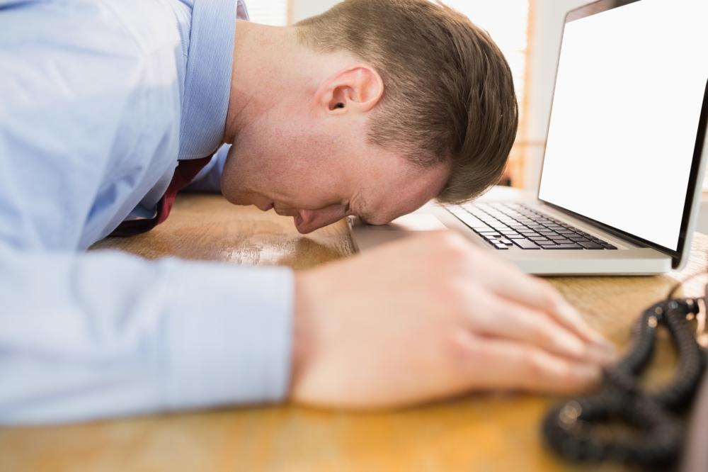 stressed-businessman-with-head-on-laptop